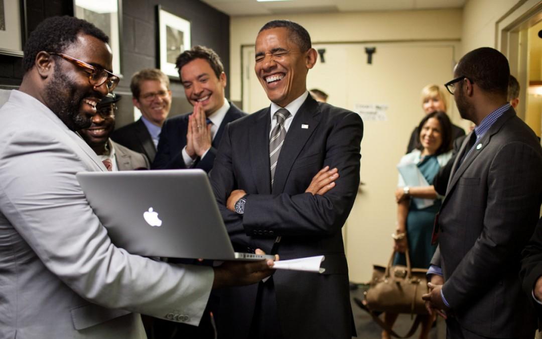 Президентът Барак Обама се смее от сърце на нещо, което негов сътрудник му показва на лаптопа.