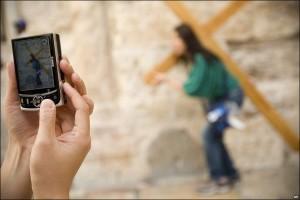 """Православна поклонничка носи кръст в близост до църквата """"Възкресение Христово"""" в Йерусалим, а жена улавя мига с фотоапарата си (http://j.mp/1mWOyy7)."""